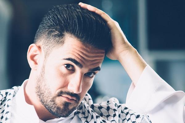 Stylish man touching combed hair with hand. Horizontal indoors shot.